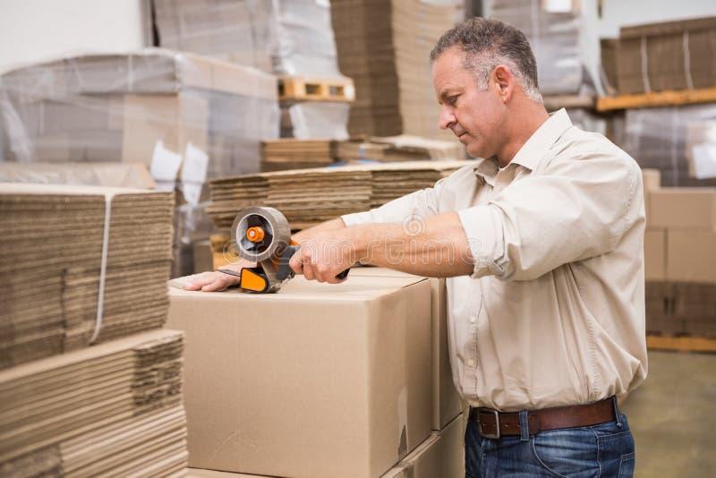 Lavoratore del magazzino che prepara una spedizione fotografia stock