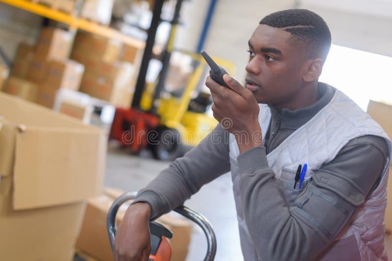 Lavoratore del magazzino di vista laterale che per mezzo del walkie-talkie fotografia stock libera da diritti