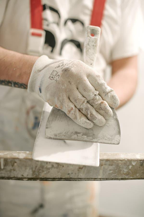Lavoratore del muratore della costruzione con la spatola ed il mortaio fotografia stock