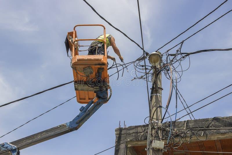 Lavoratore del palo pratico che sostituisce i cavi su un palo elettrico immagine stock libera da diritti