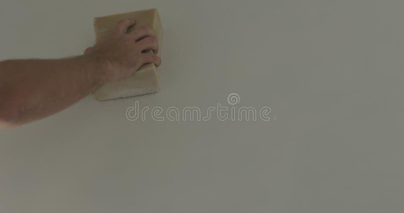 Lavoratore del primo piano che applica rivestimento protettivo su una parete fotografie stock libere da diritti
