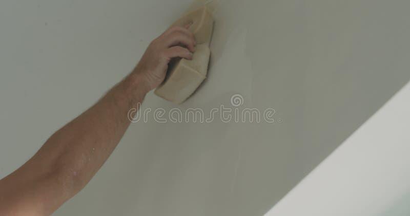 Lavoratore del primo piano che applica rivestimento protettivo su una parete fotografia stock