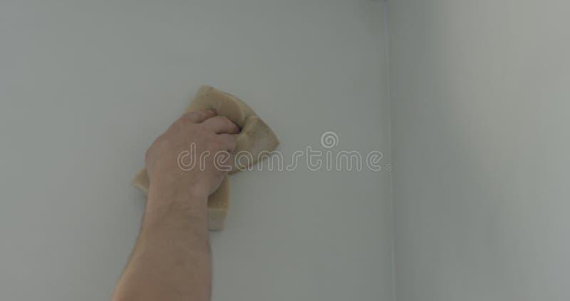 Lavoratore del primo piano che applica rivestimento protettivo su una parete immagini stock