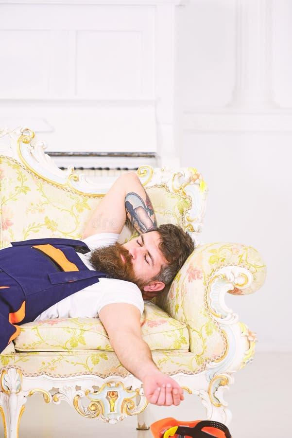 Lavoratore del primo piano con la barba, i baffi ed il tatuaggio alla moda sul suo braccio addormentato sul retro sofà Motore sta fotografie stock