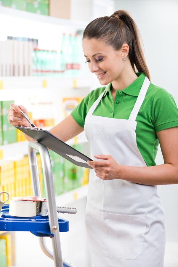 Lavoratore del supermercato con la lavagna per appunti fotografia stock libera da diritti