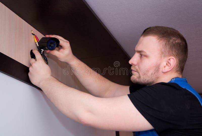 Lavoratore del tecnico che installa la macchina fotografica di videosorveglianza Primo piano della macchina fotografica del CCTV immagine stock