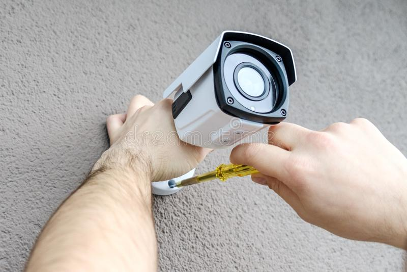 Lavoratore del tecnico che installa la video macchina fotografica del CCTV fotografia stock