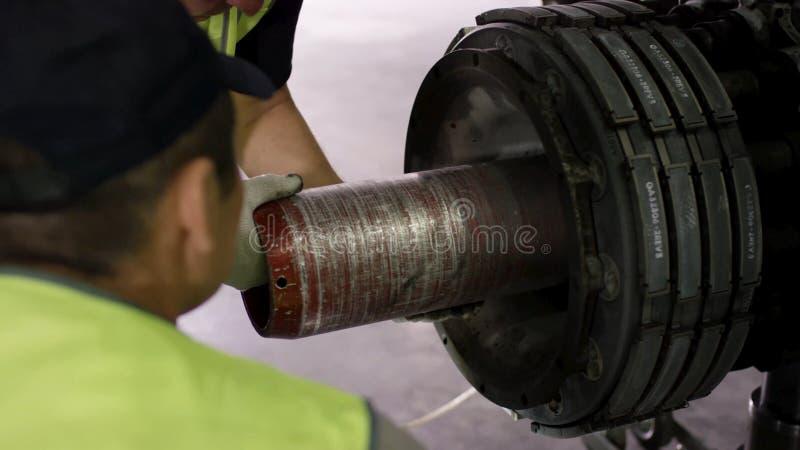 Lavoratore dell'aeroporto che controlla il telaio Motore e telaio dell'aeroplano del passeggero nell'ambito di manutenzione pesan immagine stock libera da diritti