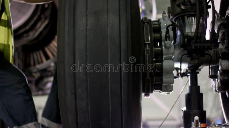 Lavoratore dell'aeroporto che controlla il telaio Motore e telaio dell'aeroplano del passeggero nell'ambito di manutenzione pesan fotografie stock