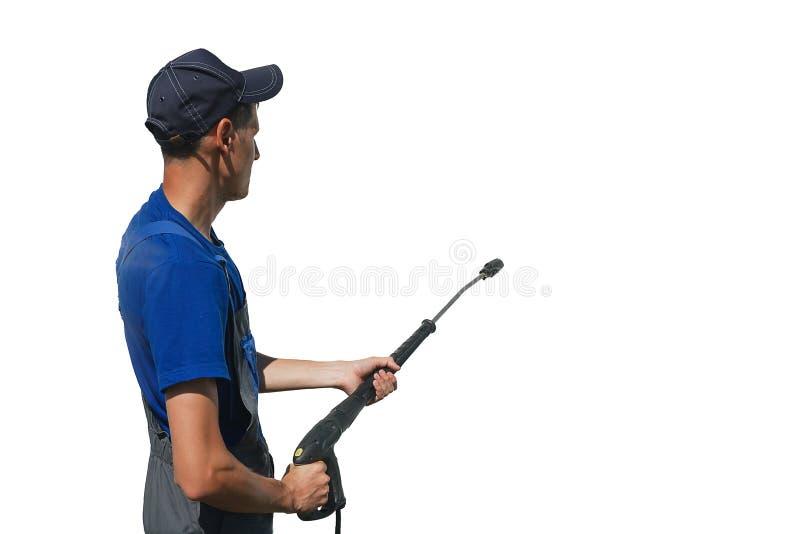Lavoratore dell'autolavaggio in camici con una pistola per lavare su un fondo bianco mentre lavorando immagine stock libera da diritti