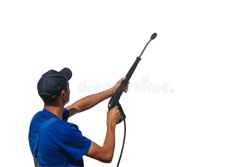 Lavoratore dell'autolavaggio in camici con una pistola per lavare su un fondo bianco mentre lavorando isolato fotografia stock