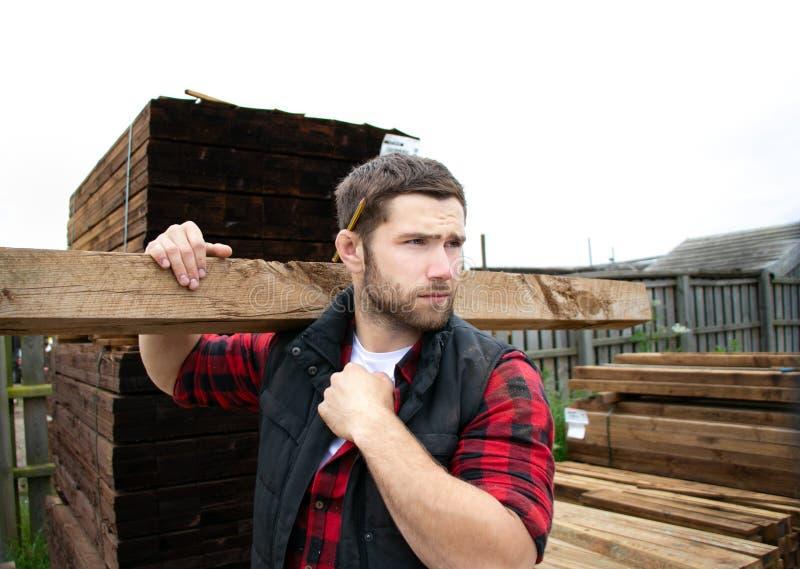Lavoratore dell'iarda di legname, carpentiere, scegliendo, tavole di legno di trasporto seclecting fotografia stock libera da diritti