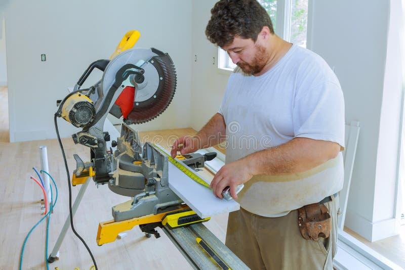 Lavoratore dell'imprenditore edile facendo uso della misurazione e del segno prima del bordo di legno della disposizione di tagli immagine stock