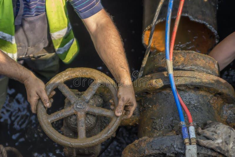 Lavoratore dell'industria che gira una valvola su un grande tubo 2 fotografia stock libera da diritti