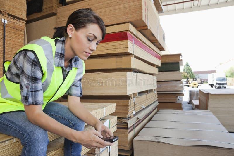 Lavoratore dell'industria femminile che per mezzo del telefono cellulare mentre sedendosi sulla pila di plance di legno immagini stock