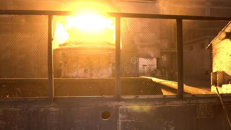 Lavoratore dell'industria siderurgica del metallo in uniforme speciale che passa attraverso i negozi metallurgici con la fornace  immagini stock