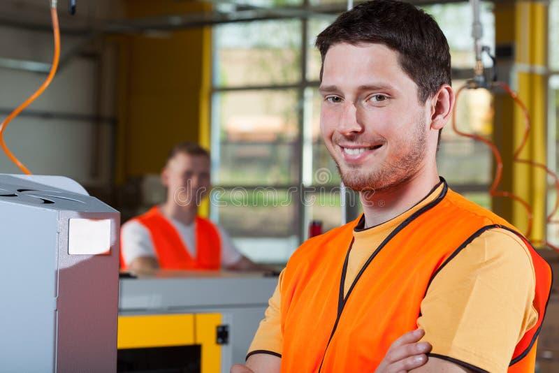 Lavoratore dell'industria sorridente alla fabbrica immagine stock libera da diritti