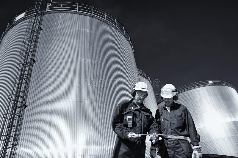 Lavoratore dell'olio con la raffineria ed i serbatoi di combustibile fotografie stock