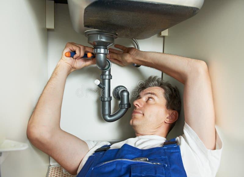 Lavoratore dell'uomo dell'idraulico con il lavandino di cucina immagine stock