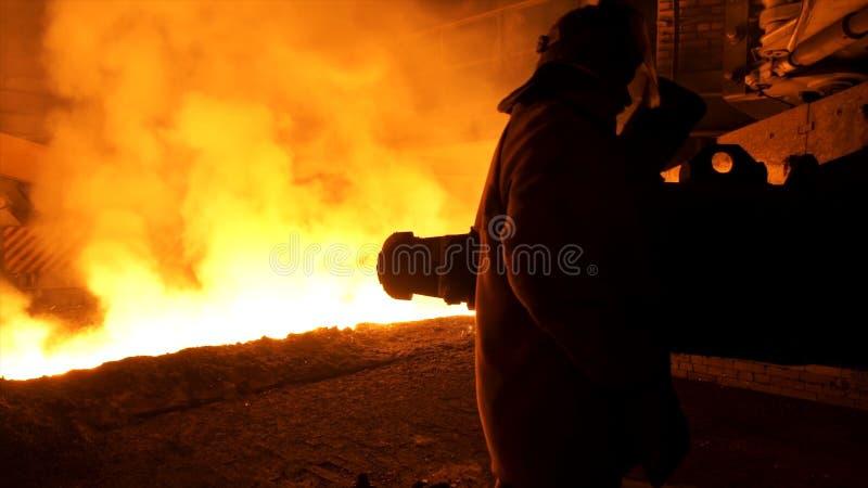 Lavoratore dell'uomo nella condizione speciale del vestiario di protezione vicino all'acciaio fuso con le scintille ed il vapore, immagini stock libere da diritti