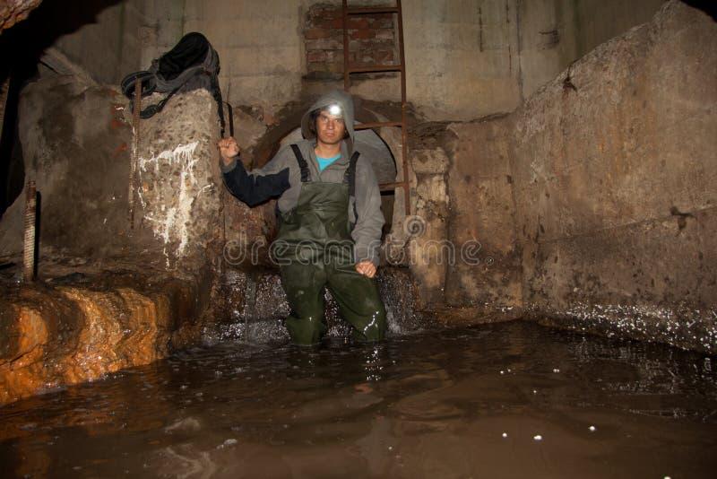 Lavoratore della fogna in collettore nel sottosuolo sommerso delle acque luride immagine stock libera da diritti