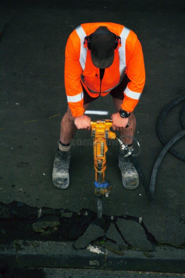 Lavoratore della strada con un trapano che tagliato su asfalto sulla strada fotografie stock libere da diritti