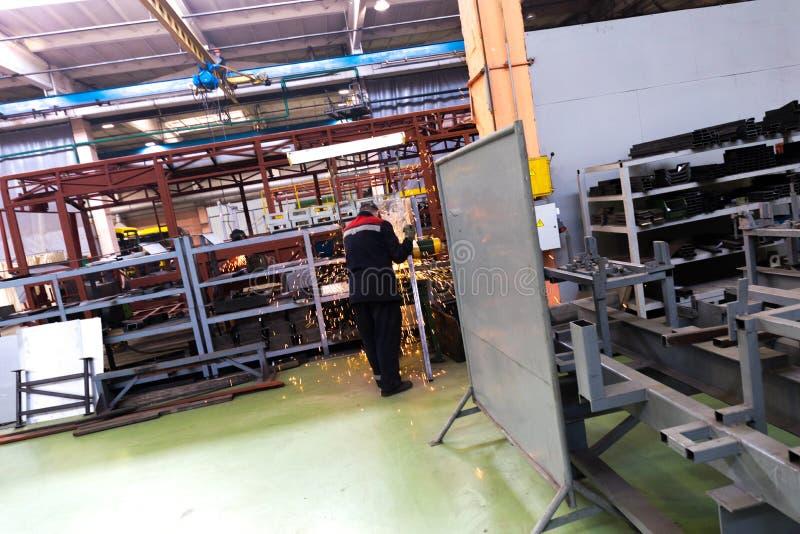 Lavoratore di industria del bus in vestiario di protezione con il braccio della saldatura sul fondo di produzione dell'automobile fotografia stock libera da diritti