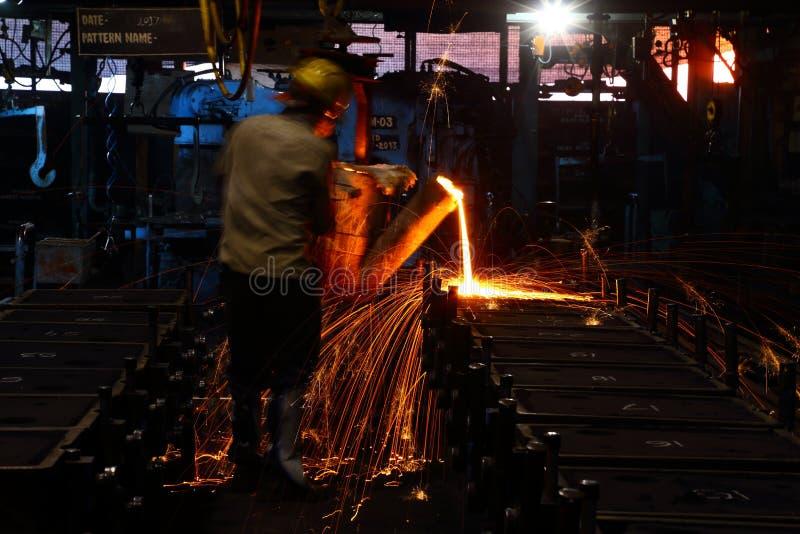 Lavoratore di versamento del metallo fotografie stock
