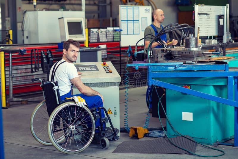 Lavoratore disabile in sedia a rotelle in fabbrica ed in collega immagine stock