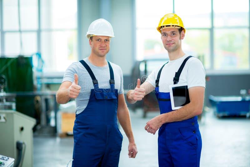 Lavoratore due in fabbrica con il pollice su fotografia stock libera da diritti