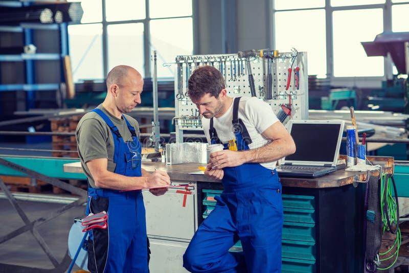 Lavoratore due in fabbrica nella conversazione immagine stock