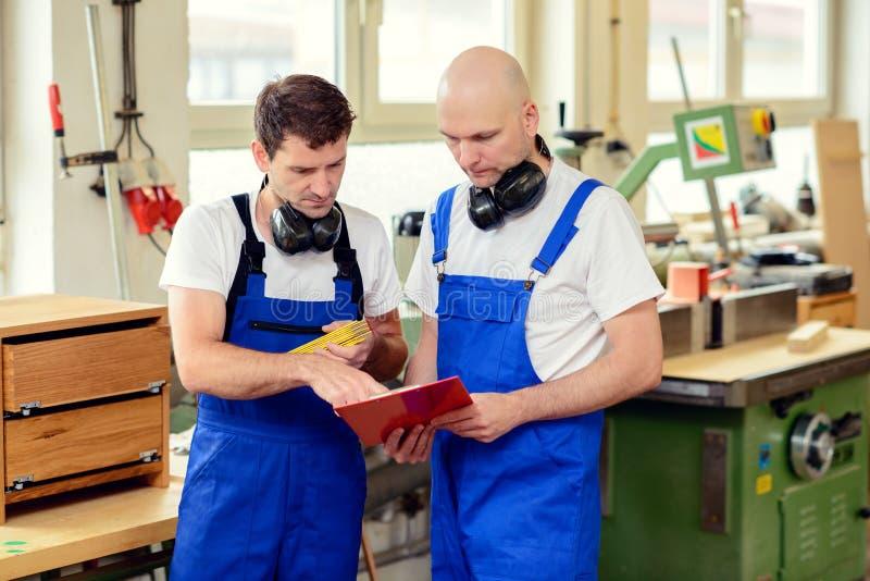 Lavoratore due in un'officina del ` s del carpentiere nella conversazione fotografie stock libere da diritti