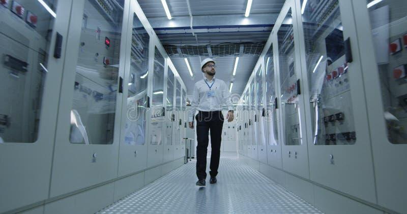 Lavoratore elettrotecnico che cammina giù il corridoio fotografie stock