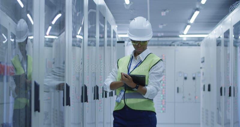 Lavoratore elettrotecnico femminile che realizza un'ispezione immagine stock
