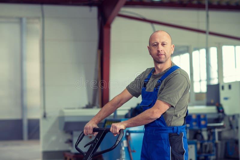 Lavoratore in fabbrica con l'ascensore della mano fotografie stock libere da diritti