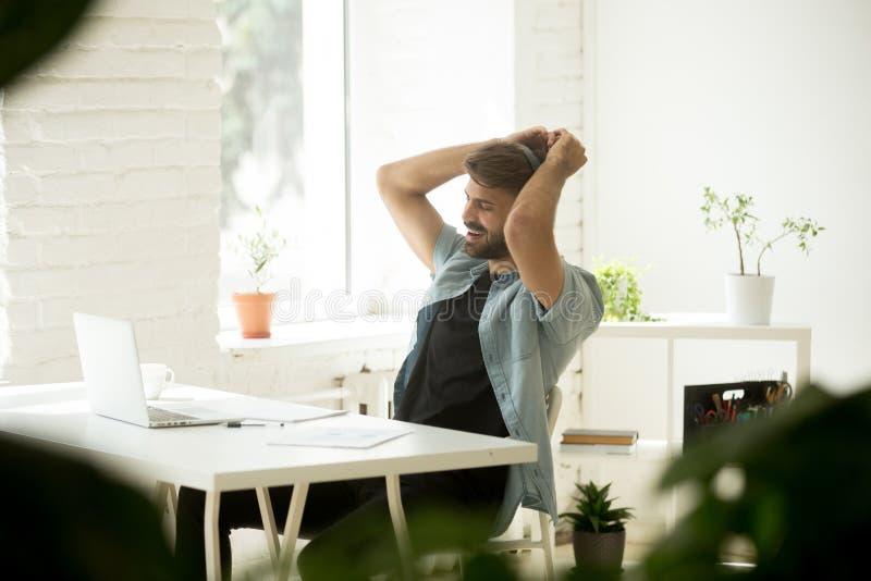 Lavoratore felice in cuffie che ascolta la musica e ballare fotografia stock libera da diritti