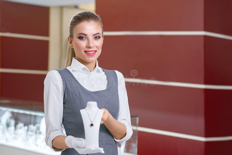 Lavoratore femminile biondo dei gioielli in guanti bianchi che mostrano collana graziosa in un negozio di gioielli moderno fotografia stock