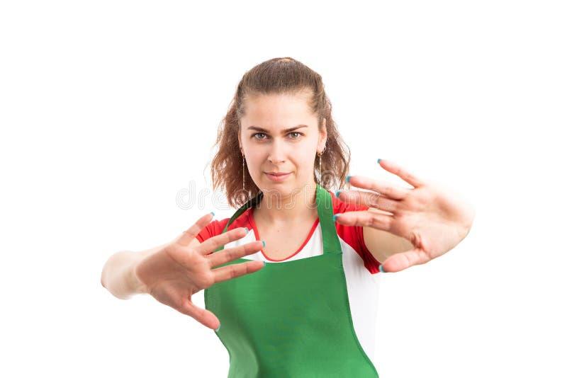 Lavoratore femminile del supermercato che fa gesto difensivo immagini stock