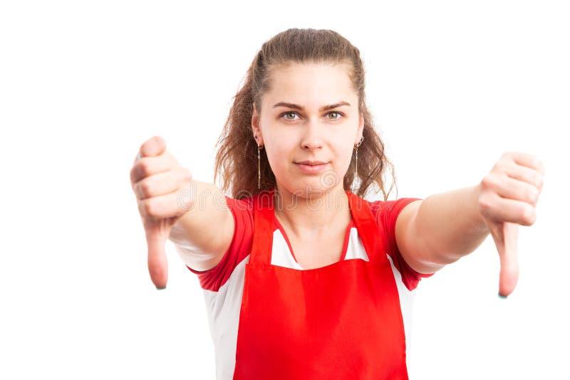 Lavoratore femminile del supermercato che mostra i pollici giù immagini stock