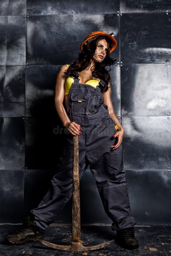 Lavoratore femminile sexy del minatore con il piccone, in tute sopra il suo corpo nudo immagini stock