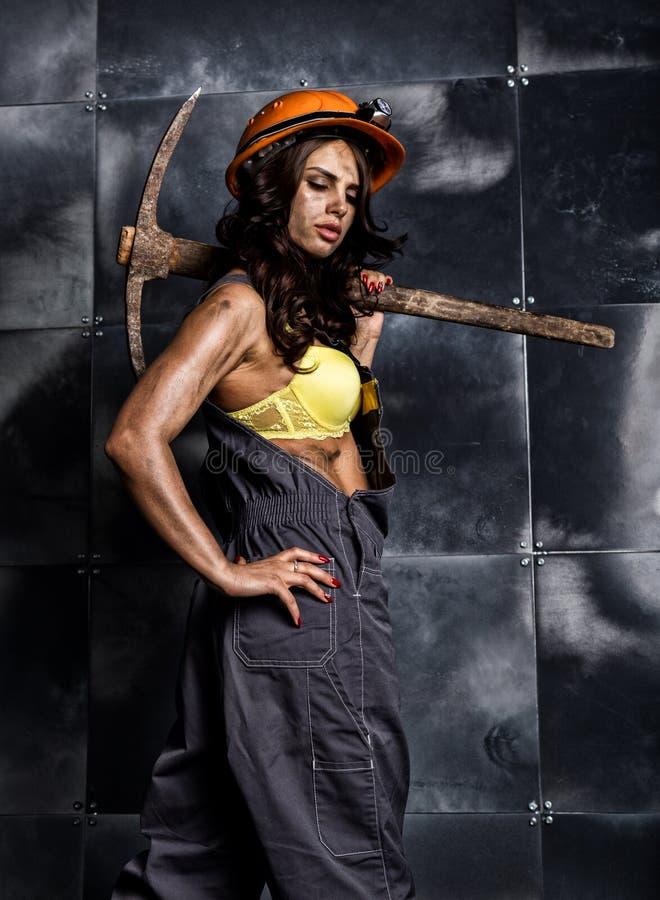 Lavoratore femminile sexy del minatore con il piccone, in tute sopra il suo corpo nudo fotografia stock