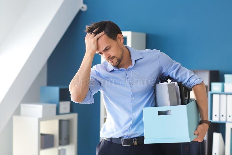 Lavoratore licenziato con roba personale in ufficio fotografie stock