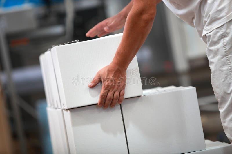 Lavoratore manuale alla linea di produzione che si occupa delle scatole fotografia stock libera da diritti