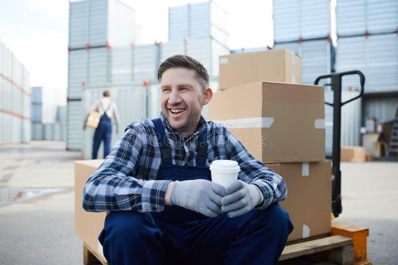 Lavoratore manuale allegro ad area all'aperto dei contenitori di stoccaggio immagini stock libere da diritti
