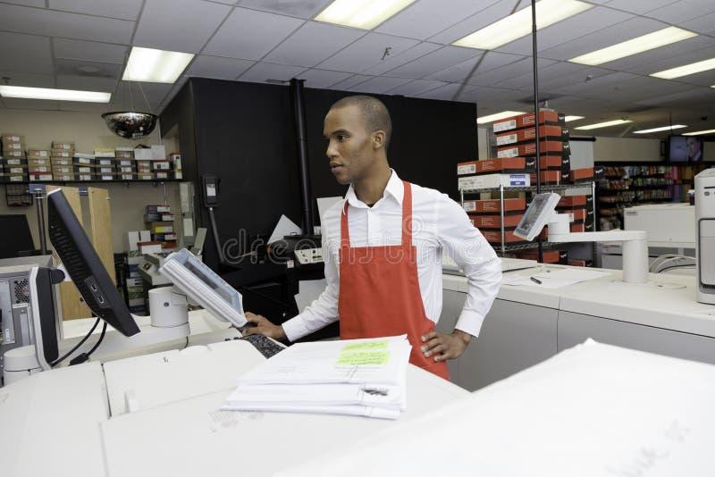 Lavoratore manuale che esamina la macchina del registratore di cassa fotografia stock