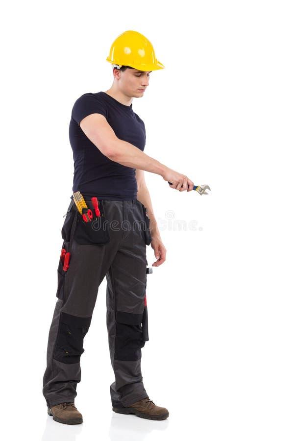 Lavoratore manuale che per mezzo di una chiave fotografia stock