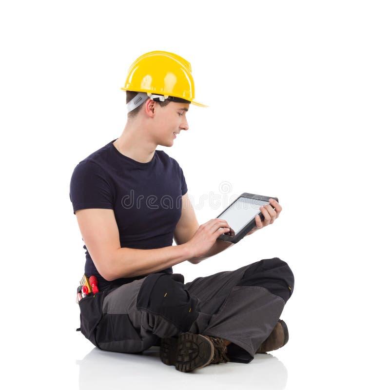 Lavoratore manuale che per mezzo di una compressa digitale fotografia stock libera da diritti