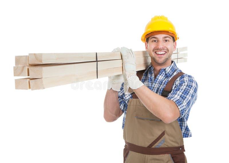 Lavoratore manuale che porta le plance di legno fotografie stock libere da diritti