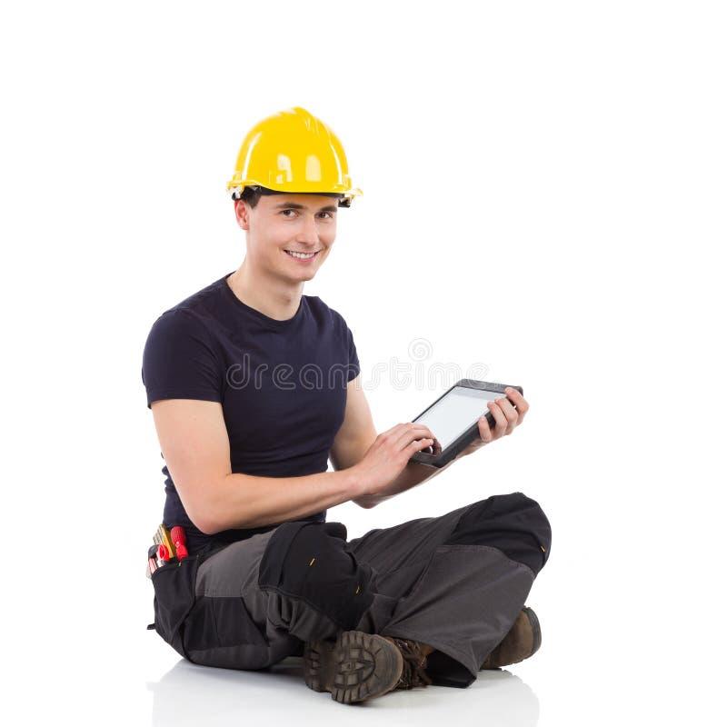 Lavoratore manuale che posa con una compressa digitale immagini stock