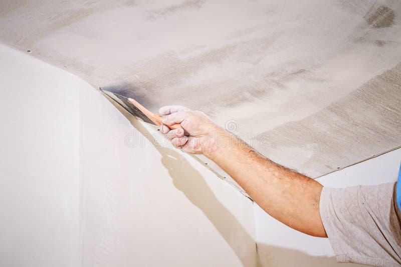 Lavoratore manuale con la parete che intonaca gli strumenti fotografie stock